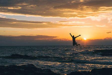 Men jump to adriatic sea durning sunset in Croatia