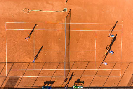 Learning to play tennis on court aerial drone photo