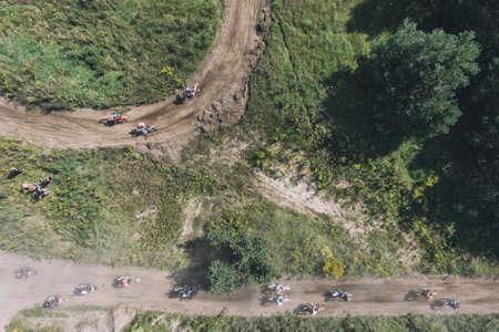 Motocross riders ride on a dust terrain track aerial drone photo Foto de archivo