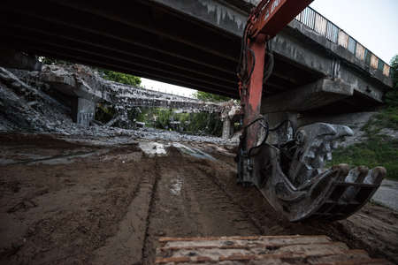 Orange excavator digger demolishing bridge