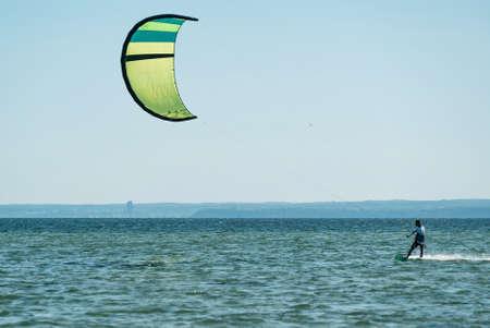 People swim in the sea on a kiteboard or kitesurfing. Summer sport learning how to kitesurf. Kite surfing on Puck bay in Jastarnia, Poland, Europe
