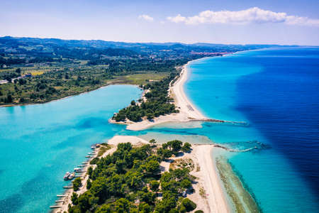 Beautiful Beach With Golden Sand And Clear Water. Turquoise coast with blue water and golden sand in Europe. Summer vacation background with turquoise sea water bay and pine trees aerial drone photo view