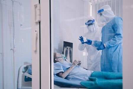 Infected patient on takecare of Doctor and nurse with x-ray Lung in quarantine lying on bed in hospital from coronavirus covid 19 disease. Covid19 or corona virus is world global social issue concept. Stock Photo