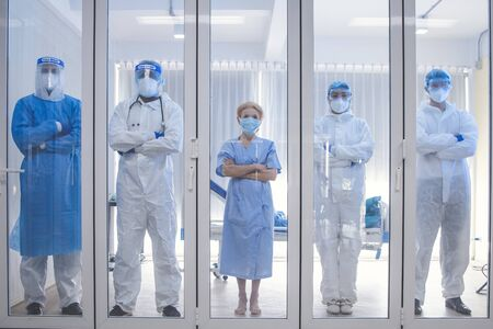 5 of Doctor, Nurse and patient looking out in the quarantine room from case of coronavirus covid 19. Virus infected patient with outbreak at hospital with coronavirus covid 19 disease treatment. Stock Photo