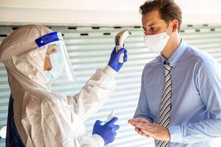 Alignez-vous pour le concept de distanciation sociale. L'agent utilise un thermomètre frontal infrarouge pour vérifier la température corporelle de la fièvre afin de détecter les symptômes du virus. Maladies respiratoires telles grippe covid19, coronavirus. Banque d'images