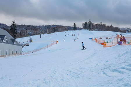 Area of Kiroro ski resort. Skiers and Snowboarders Ride the Gondola at Kiroro Ski Resort during winter with fully of snow ground in Hokkaido, Japan. 免版税图像 - 156609154
