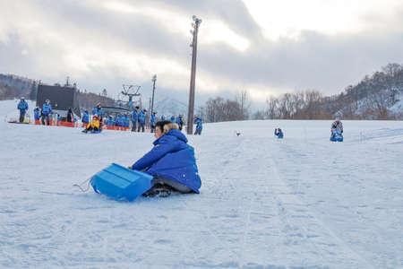 Hokkaido, Japan - December 2019 : Photo of a family and children are playing ski sliders together in the Mountain Club ski resort of The Kiroro hotel in Sapporo, Hokkaido Japan 新闻类图片