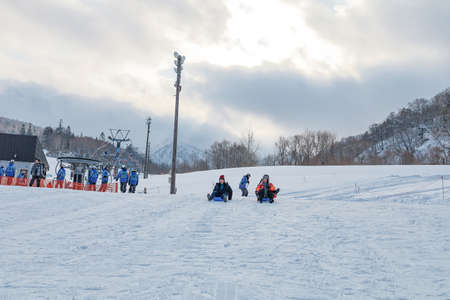 Hokkaido, Japan - December 2019 : Photo of a family and children are playing ski sliders together in the Mountain Club ski resort of The Kiroro hotel in Sapporo, Hokkaido Japan 免版税图像 - 156652179