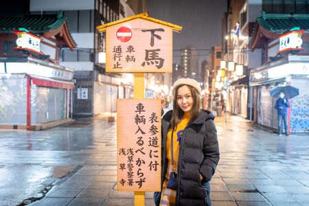 Asakusa, Tokyo, Japan - February 2020 : Pretty Girl is standing under Red Lantern of Sensoji Temple's Kaminarimon gate at main entrance Asakusa, Tokyo, Japan is famous detination for toursit visit at 新闻类图片