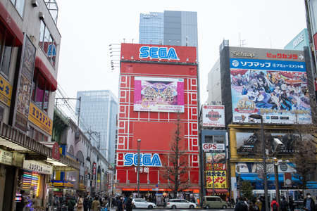 Tokyo, Japan - February 2020: Neon lights and billboard advertisements on buildings at Akihabara at rainy night. Akihabara is a shopping district for video games, anime, manga, and computer goods.