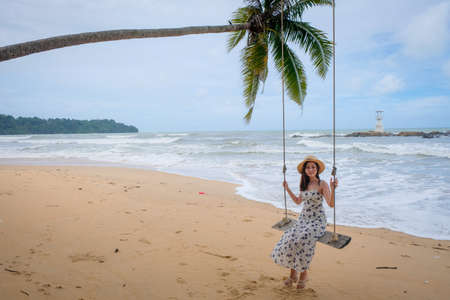 Pretty girl on swing with backgound of Nang Thong Beach in Khao lak lighthouse at Phang Nga Province, Thailand. There are beautiful rocks sparsely, soft white sand. 免版税图像