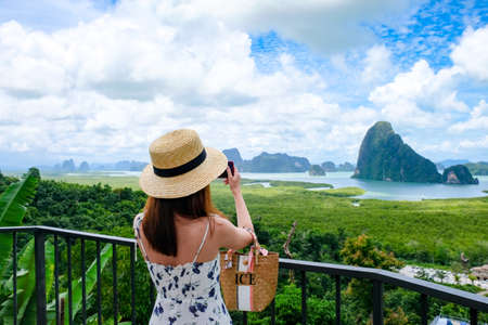 Happy Young Traveler Woman Raised Arm take a photo To Sky Enjoying A Beautiful Of Nature Samed Nang Chee on mountain landscape view point at jame bond island seascape at Antaman sea in thailand.