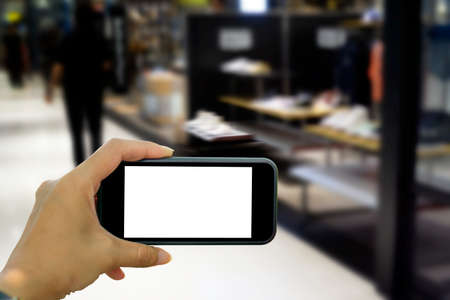 Shopping hand holding mobile empty black screen horizontal the phone shopping in department store background abstract motion blurred concept