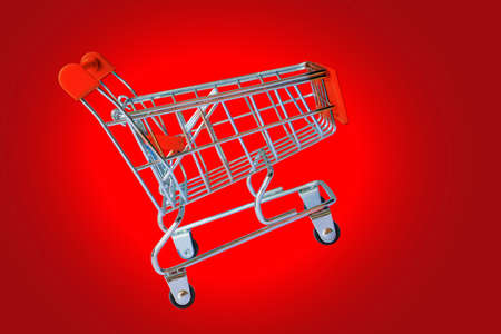 Empty shopping cart parking on red background with copy space