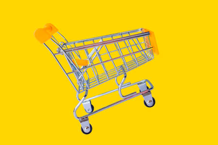 Empty shopping cart parking on yellow background with copyspace Banco de Imagens