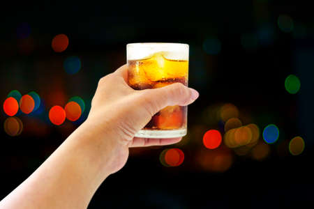 Glass of whiskey drink with ice cube Bokeh background Banco de Imagens