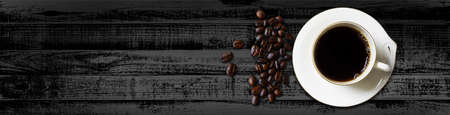 Cup of coffee and coffee beans, on black wood top view - Web Banner Banco de Imagens