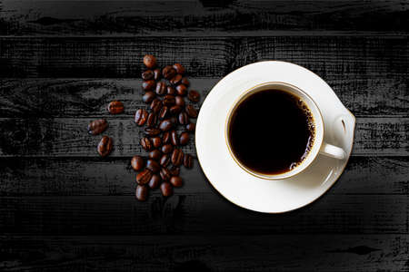 White cup of roasted coffee beans on black background
