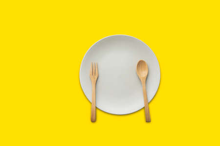 Dish with a wooden spoon on a yellow background
