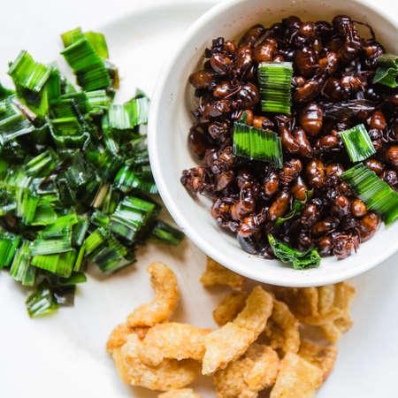 hormigas subterráneas fritos con chicharrón y hojas de pandanus. Foto de archivo