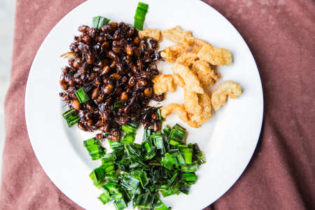 Fried subterranean ants with pork crackling and pandanus leafs.