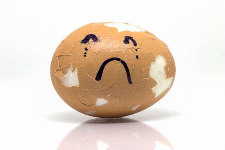 Eggs broken in sad emotion on isolate white background. Foto de archivo