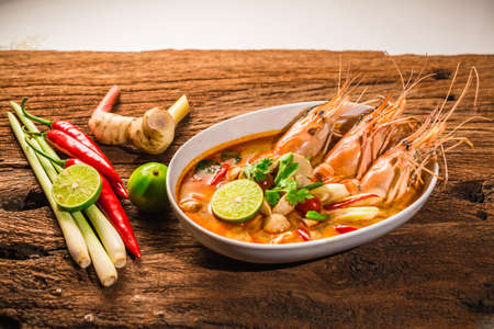favorite soup: Tom Yum Goong Thai hot spicy soup shrimp  with lemon grass,lemon,galangal on wooden background Thailand Food Stock Photo