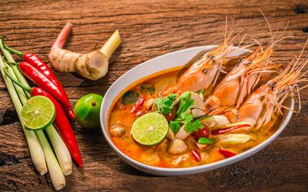 Tom Yum Goong Тайский горячий пряный креветки супа с лимонной травой, лимон, галангал на деревянном фоне Таиландская еда