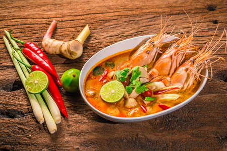 Tom Yum Goong Thai hot spicy soup shrimp  with lemon grass,lemon,galangal on wooden background Thailand Food Standard-Bild