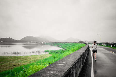 reservoirs: Young women walking on streets of large reservoirs with the mountain early in the morning at Thailand, color effect photo.