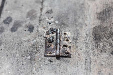 Old Steel hinge on concrete ground. Stock Photo