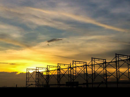 Silhouette of scaffolding in the construction site before to night time or sunset time. worker empty. Building under construction and the construction crane or  power crane