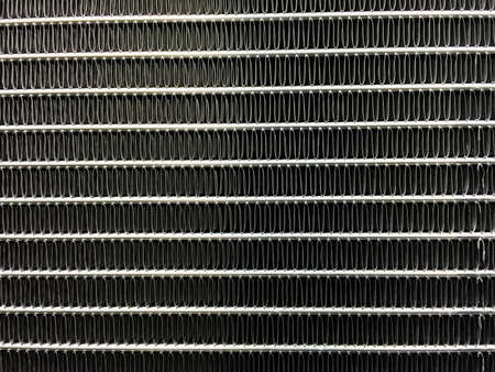 exchanger: Condenser unit used in central air conditioning systems - heat exchanger (heat micro canel) section to cool down and condensate incoming refrigerant vapor into liquid. background  texture. Air conditioner technology. Stock Photo
