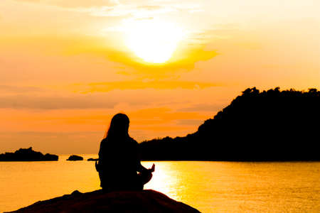 karnataka: Silhouette, Woman Meditating in Yoga pose or Lotus Position by the Sea at Sunset. Rear View. Nature Meditation Concept. Low key photo. relax time. Stock Photo