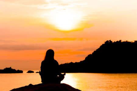 Silhouette, Woman Meditating in Yoga pose or Lotus Position by the Sea at Sunset. Rear View. Nature Meditation Concept. Low key photo. relax time. Stock Photo