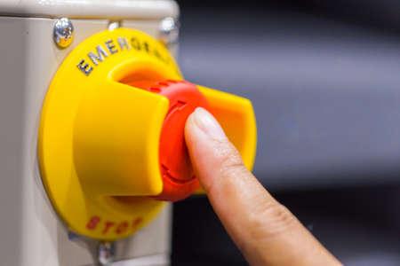 赤い緊急ボタンや停止ボタンを押すと手。産業機械、安全のため緊急停止のボタンを停止します。