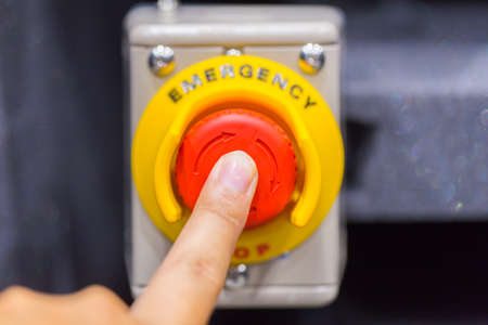 Hand pressing the red emergency button or stop button. STOP Button for industrial machine, Emergeny Stop for Safety.
