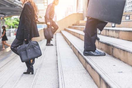 Homme d'affaires et femme dans les escaliers dans une heure de pointe d'affaires pour travailler.