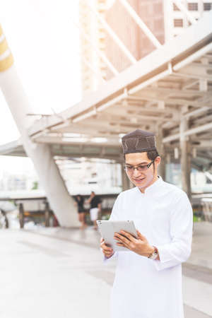 Young handsome businessman Arab Muslims looking at his business report in his tablet by internet network while standing at central of city. Business and technology concept. Imagens