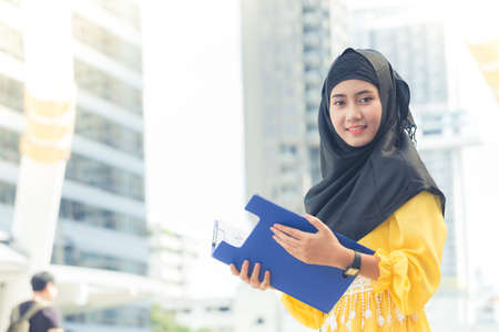 headcloth: Young asian muslim business woman smiling and holding file document and standing at capital city. Beautiful muslim women. Thai muslim women.
