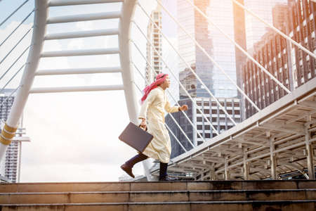 rapidly: Young Muslim business man  holding bag and running rapidly to airport. In rush hour at stairway in urban. Business in the city concept. Stock Photo