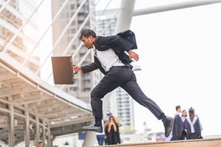 rapidly: Motion blur of Businessman  holding bag and running rapidly to airport in formal suit. In rush hour at stairway in city. Business in the city concept.