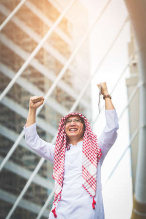 Business winner concept, Two Young muslim business man standing by raising both hands up in urban and demonstrated success in their business. Stock Photo