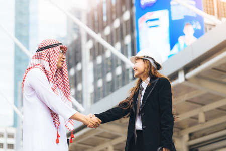 handclasp: Business success concept. Asian muslim businessman and Engineer woman making handshake or holding hand together to agree joint business and partnership.