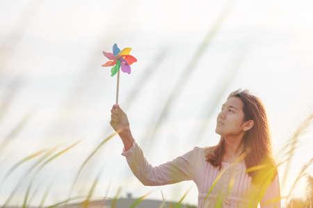 朝の冬のシーズンの草原で風グッズまたは風タービンや風車とウールの帽子を持って美しい女の子のシルエット。 写真素材