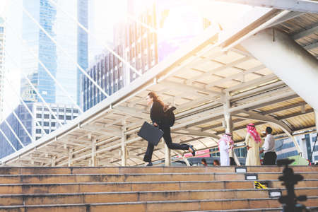 rapidly: Business woman  holding bag and running rapidly to airport in formal suit. In rush hour at stairway in city. Business in the city concept. Stock Photo