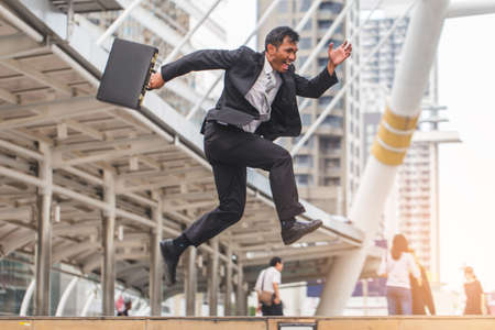 rapidly: Businessman  holding bag and running rapidly to airport in formal suit. In rush hour at stairway in city. Business in the city concept.