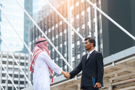 handclasp: Business success concept. Asian muslim businessman and Engineer man making handshake or holding hand together to agree joint business and partnership. Stock Photo