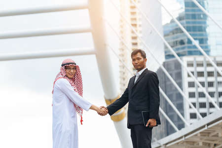 Business success concept. Asian muslim businessman and Engineer man making handshake or holding hand together to agree joint business and partnership. Stock Photo