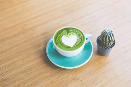 Hot matcha green tea with heart shape latte art in green cup and cactus on wood table. Love conception. Stock Photo